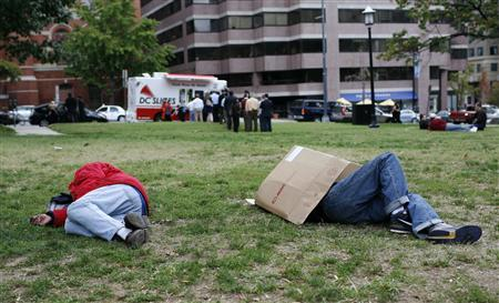 Homeless men sleep in a park while people wait in line to purchase pizza from a pizza mobile in Washington, October 21, 2010. REUTERS/Molly Riley