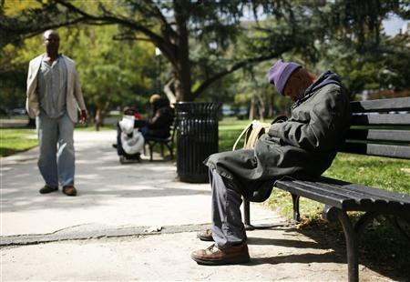 A homeless man snoozes on a bench in a park in Washington, October 21, 2010. REUTERS/Molly Riley