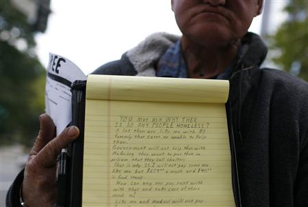 A homeless man who cannot speak, holds up a piece of paper explaining his reasons why so many people are homeless, in Washington, October 21, 2010. REUTERS/Molly Riley