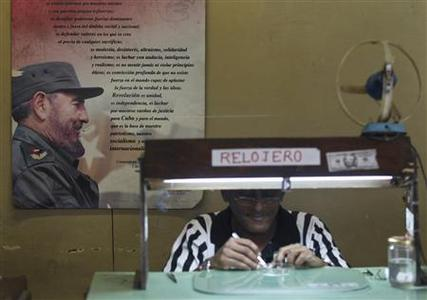 A portrait of former Cuban leader Fidel Castro is seen on the wall as a watchmaker works at his stall in Havana October 22, 2010. REUTERS/Enrique De La Osa