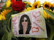 <p>A card with a photograph of late entertainer Michael Jackson is placed among flowers during an event to commemorate the first anniversary of his death, in Leipzig, June 25, 2010. REUTERS/Fabrizio Bensch</p>