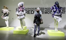 <p>A woman inspects clothes at an exhibition of creations made by students of La Cambre fashion school in Brussels October 23, 2010. REUTERS/Sebastien Pirlet</p>