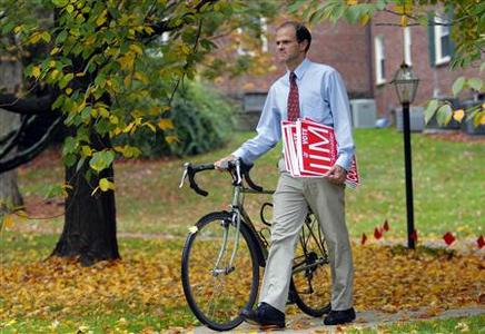 Jim Schneller, a self-avowed Tea Party activist, walks near his campaign headquarters with his bicycle and campaign signs in Wayne, Pennsylvania, October 27, 2010. REUTERS/Tim Shaffer