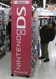 <p>Un cliente busca un videojuego en la repisa de Nintendo DS en una tienda en Tokio. Oct 28 2010 Nintendo informó el jueves de que había reducido a la mitad sus beneficios trimestrales, bastante en línea con las expectativas después de que recortara sus previsiones el mes pasado por un yen fuerte y retrasara el lanzamiento de su videoconsola con capacidad 3D. REUTERS/Issei Kato</p>