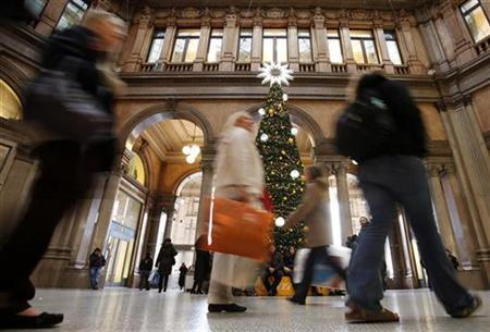 Shoppers walk past a Christmas tree in a shopping arcade in downtown Rome December 21, 2009. REUTERS/Alessia Pierdomenico