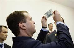 <p>Президент России Дмитрий Медедев рассматривает купюру номиналом 1.000 рублей в Санкт-Петербурге 7 ноября 2008 года. По меньшей мере пятая часть расходов на казенные закупки в России оседает в карманах коррупционеров, и откаты превышают 1 триллион рублей ($32 миллиарда) в год, признал Кремль. Ровно на такую сумму чиновники решили повысить налоги со следующего года. REUTERS/RIA Novosti/Kremlin/Dmitry Astakhov</p>