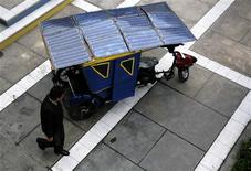 """<p>Un hombre pasa frente a una 'mototaxi' solar en la Universidad de San Marcos en Lima, oct 28 2010. Un profesor universitario de Perú desarrolló un modelo de """"mototaxi"""" impulsado con energía solar o baterías eléctricas, que podría reducir la contaminación y costos del popular medio de transporte de pasajeros en el país. Mariana Bazo/ REUTERS</p>"""
