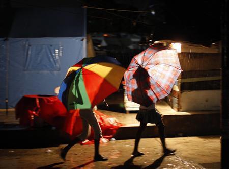 Residents walk under rain at down town Port-au-Prince October 31, 2010. REUTERS/ Eduardo Munoz