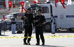 <p>Riot police stand guard as police forensic officers inspect the scene after an explosion near the police vehicles in central Istanbul October 31, 2010. A suspected suicide bomber injured at least 15 people in the explosion in Istanbul's central Taksim Square on Sunday, Turkish media reported. REUTERS/Murad Sezer</p>