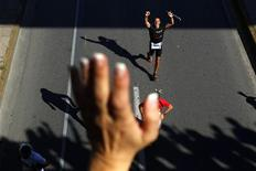 <p>A marathon runner acknowledges cheering spectators while running under a bridge close to the end of the Athens Classic Marathon October 31, 2010. REUTERS/Yannis Behrakis</p>