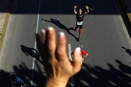 A marathon runner acknowledges cheering spectators while running under a bridge close to the end of the Athens Classic Marathon October 31, 2010. REUTERS/Yannis Behrakis