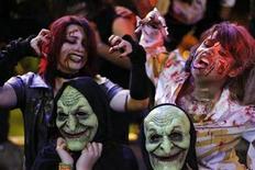 """<p>Un grupo de personas vestidas como zombis durante el desfile de noche de brujas en San José, Costa Rica, oct 31 2010. Apenas un día después de Halloween dos dentistas de Pensilvania están ofreciendo un programa para recompra de dulces para proteger los dientes de los niños que pidieron """"dulce o travesura"""" y animar a los soldados estadounidenses en Irak y Afganistán. REUTERS/Juan Carlos Ulate</p>"""