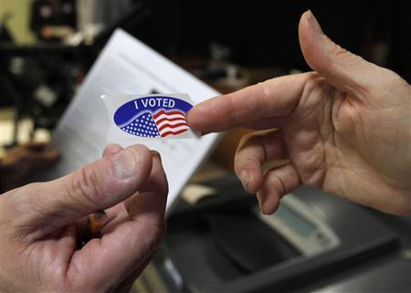 A volunteer (R) hands a sticker to an early voter for the U.S. midterm elections at a polling place in Washington November 2, 2010. The sticker is given to voters after they have submitted their ballot. REUTERS/Jason Reed