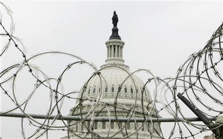 The U.S. Capitol sits beyond barbed wire at a construction site entrance on the Capitol grounds on the day of the U.S. midterm congressional elections in Washington November 7, 2006. REUTERS/Jim Bourg