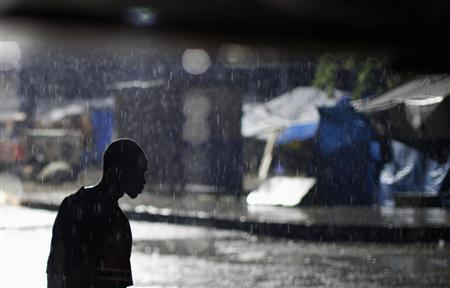 A man walks in the rain at downtown Port-au-Prince October 31, 2010. REUTERS/ Eduardo Munoz