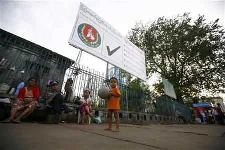 People pass the time in front of an election billboard in central Yangon November 2, 2010. REUTERS/Soe Zeya Tun