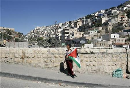 A Palestinian boy holds a flag after a visit of Israeli parliament members to the mostly Arab neighbourhood of Silwan in East Jerusalem October 12, 2010. REUTERS/Ammar Awad