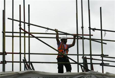 A worker takes down scaffolding on a construction site in London August 27, 2010. REUTERS/Luke MacGregor