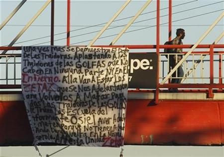 A man walks by a banner hung by suspected hitmen from the Zetas gang at a pedestrian bridge in Monterrey November 6, 2010. Suspected hitmen from the Zetas gang hung messages between trees and over bridges in Reynosa and in cities across northeastern Tamaulipas state, mocking rival Gulf Cartel gang leader Ezequiel ''Tony Tormenta'' Cardenas' death, who was shot dead by marines on Friday. The banner, mainly in slang, celebrates the death of Cardenas. REUTERS/Tomas Bravo