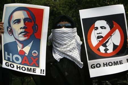 A man holds placards during a protest against President Barack Obama's upcoming visit to Indonesia, in Jakarta November 9, 2010. REUTERS/Dadang Tri