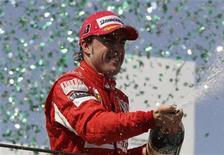 """<p>Автогонщик """"Феррари"""" Фернандо Алонсо празднует третье место в гонках в Бразилии, Сан-Паулу 7 ноября 2010 года. Завершающий этап автогонок в классе """"Формула 1"""" пройдет в ближайшие выходные в Абу-Даби, и математические шансы на чемпионский титул сохраняют четыре пилота. REUTERS/Bruno Domingos</p>"""