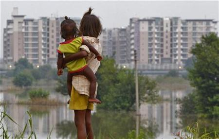 A girl carrying a child stands outside her makeshift tent in front of the athletes village of the 2010 Commonwealth Games, while surrounded by flood waters of the river Yamuna in New Delhi September 23, 2010. REUTERS/Andrew Caballero-Reynolds