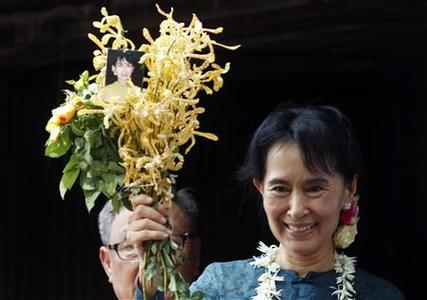 Aung San Suu Kyi holds a bunch of flowers before addressing supporters outside the headquarters of her National League for Democracy party in Yangon November 14, 2010. REUTERS/Soe Zeya Tun