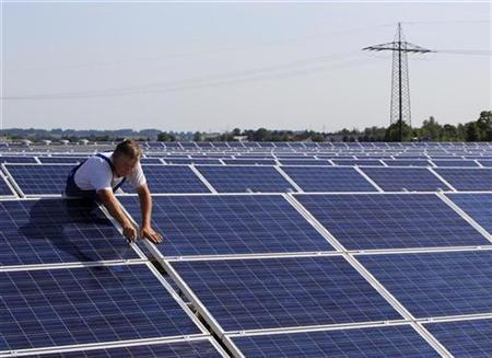 A construction worker fixes solar panels for a new solar power plant near Olching-Esting westward of Munich July 7, 2010. REUTERS/Michaela Rehle