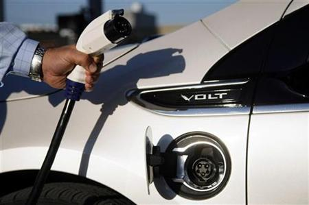 A General Motor Co employee shows the plug from a newly installed electric vehicle charging station for the Chevrolet Volt outside GM's world headquarters in Detroit, Michigan October 12, 2010. REUTERS/Rebecca Cook