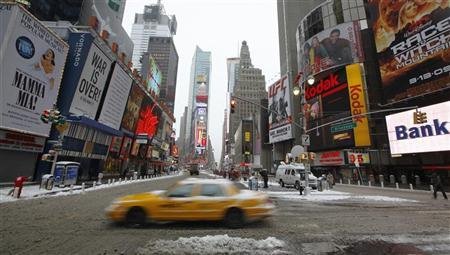 A taxi crosses Times Square after a snowstorm blanketed the eastern United States with as much as a foot of snow, in New York March 2, 2009. REUTERS/Chip East (UNITED STATES)