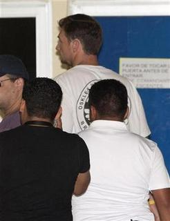Mexican police escort Bruce Beresford-Redman (C), a former producer of the ''Survivor'' television series, inside Quintana Roo's attorney general's office in Cancun, April 8, 2010. REUTERS/Gerardo Garcia