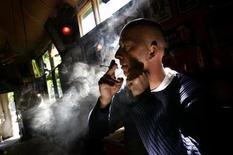 <p>Мужчина курит марихуану в кофешопе в Роттердаме 14 июня 2005 года. Правительство Нидерландов в среду заявило о своем желании запретить продажу марихуаны в кофешопах туристам. REUTERS/Jerry Lampen</p>
