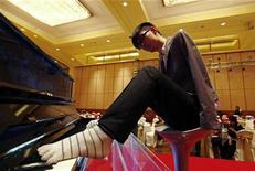 <p>Pianist Liu Wei who is armless, plays piano with his toes during a practice session for a promotional event for a local television channel, in Beijing, November 15, 2010. REUTERS/Petar Kujundzic</p>