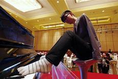 <p>Liu Wei, un jeune pianiste chinois privé de ses deux bras, s'apprête à partir en tournée mondiale pour présenter son art de jouer avec les orteils. /Photo prise le 15 novembre 2010/REUTERS/Petar Kujundzic/Files</p>