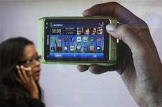 <p>Женщина проходит мимо рекламы смартфона Nokia N8 в Лондоне, 30 сентября 2010 года. Часть новых смартфонов Nokia N8 поступила в продажу с дефектом в системе питания, приводящей к самоотключению аппарата, сообщила Nokia в пятницу. REUTERS/Luke MacGregor</p>
