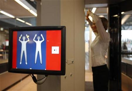 A security official demonstrates a full body scanner during a photocall at Departure Gate 2 at Hamburg Airport in Hamburg September 27, 2010. REUTERS/Christian Charisius