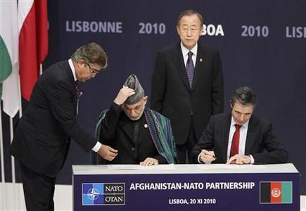 Afghanistan's President Hamid Karzai (2nd L) and NATO Secretary General Anders Fogh Rasmussen (R) sign accords in front of U.N. Secretary General Ban Ki-moon during the NATO Summit in Lisbon November 20, 2010. REUTERS/Yves Herman
