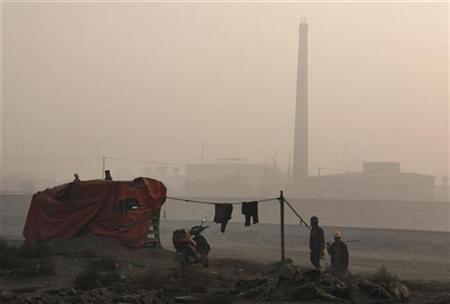 Workers walk through thick haze in front of a rare earth smelting plant next to a vast tailings dam near Xinguang Village, located on the outskirts of the city of Baotou in China's Inner Mongolia Autonomous Region October 31, 2010. REUTERS/David Gray
