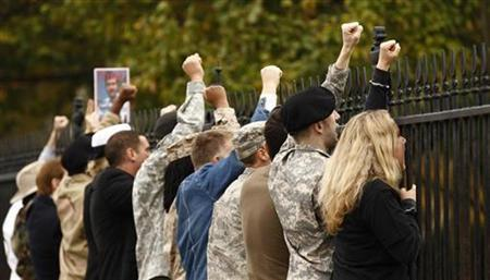 In an act of civil disobedience, demonstrators handcuff themselves to the fence at the White House and shout their protests against the military's ''don't ask, don't tell'' policy in Washington November 15, 2010. REUTERS/Kevin Lamarque
