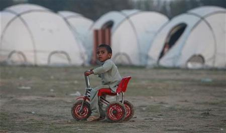 Amirzada, a three-year-old Afghan boy displaced by floods nearly two months earlier, sits on his bicycle near his family tent at a relief camp in Charsadda, in Pakistan's Khyber Pakhtunkhwa province September 28, 2010. REUTERS/Faisal Mahmood