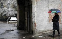<p>Женщина укрывается под зонтом от мокрого снега, Москва 17 ноября 2009 года. Заморозки и большое количество осадков ждут Москву во время текущей рабочей недели, прогнозируют синоптики. REUTERS/Denis Sinyakov</p>