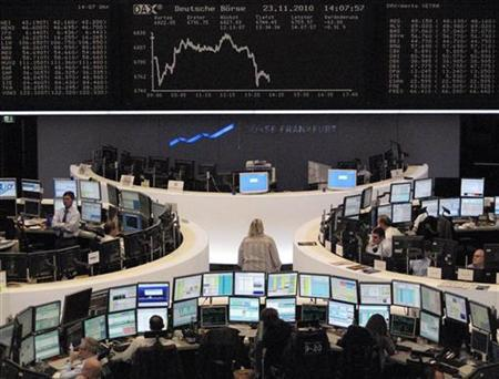 Traders are pictured at their desks in front of the DAX board at the Frankfurt stock exchange November 23, 2010. REUTERS/Remote/Amanda Andersen