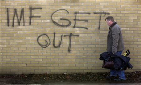 A man carrying his tools walks near a graffiti in South Dublin November 23, 2010. REUTERS/Cathal McNaughton