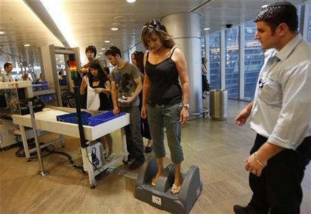 An Israeli woman stands on a step-on scanner during a security check at Ben Gurion airport near Tel Aviv October 12, 2008. REUTERS/Gil Cohen Magen