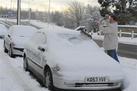 A man clears his car of snow at Bowburn, northern England November 28, 2010. REUTERS/Nigel Roddis