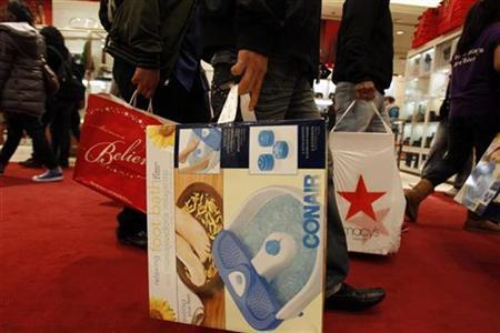 Shoppers carry their Black Friday purchases as they leave Macy's in New York November 26, 2010. REUTERS/Jessica Rinaldi