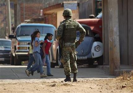 A soldier stands guard as girls walk past in Morelia November 24, 2010. REUTERS/Leogivildo Gonzalez