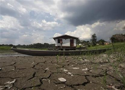 A fisherman stands at his floating house in Caapiranga, in Amazonas state, northern Brazil, in this November 3, 2010 file photo. REUTERS/Ricardo Moraes