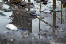 <p>Un cartello stradale che indica la direzione per Pompei riflesso in una pozzanghera. REUTERS/Alessandro Bianchi</p>