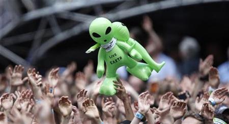 A spectator holds up inflatable aliens during the Live Earth concert at Wembley Stadium, London July 7, 2007. REUTERS/Stephen Hird